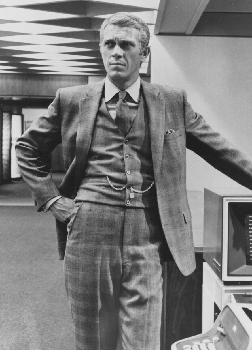McQueen standing by a computer from the era