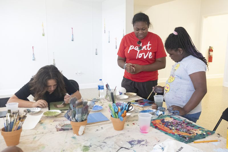 Chloe Young works with Emily Stevens, 13 (L) and Nydia Jones, 9 (R) on a self-portrait project around the theme of self expression.