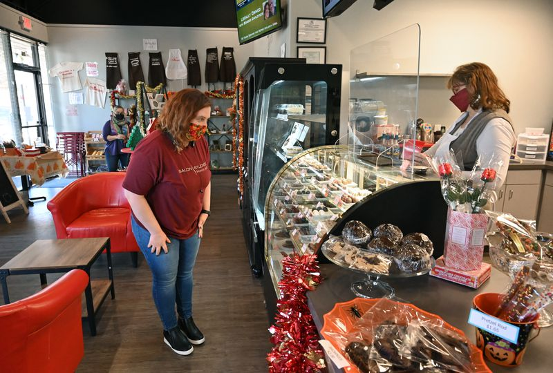 November 6, 2020 Roswell - Jennifer Seaman (left), tries to choose chocolates to buy as M.J. O'Neill, owner, assists at Chamberlain's Chocolate Factory in Roswell on Friday, November 6, 2020. (Hyosub Shin / Hyosub.Shin@ajc.com)
