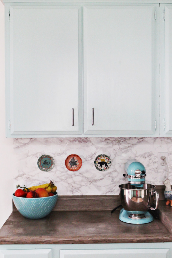 A DIY kitchen remodel featuring mint cabinets, concrete countertops and colorful accents. Whole kitchen and dining room done for less than $700 (including floor)! via ajoyfulriot.com