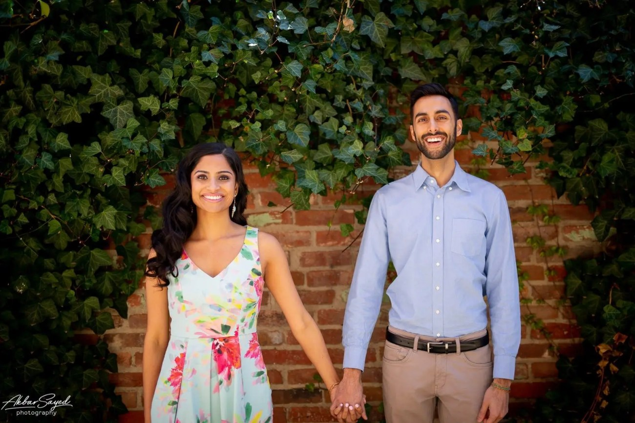 Old Town Alexandria engagement photo with an engaged Indian - American couple against a brick wall with vines.