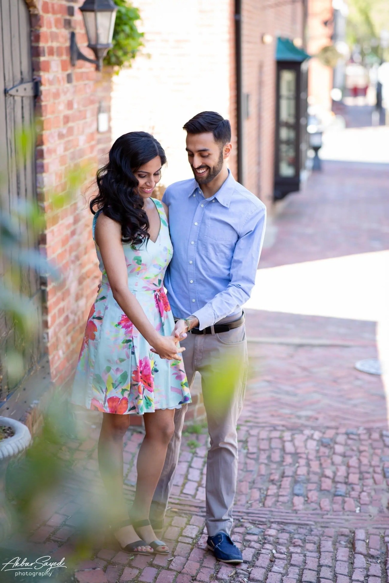 Old Town Alexandria engagement photo with an engaged Indian - American couple against a brick wall.