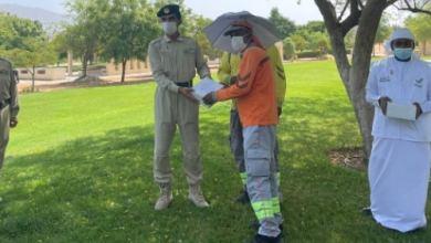 شرطة دبي توزع قبعات مظلة ووجبات على العمال - الأخبار