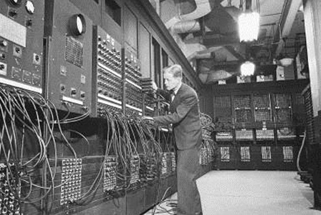 man working on room-size computer
