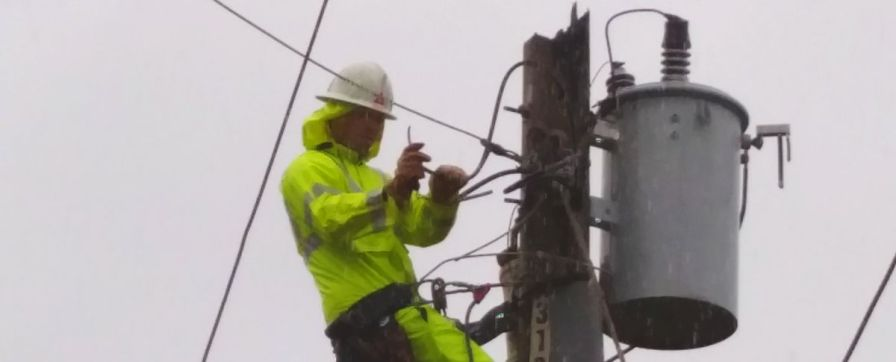 Lineman works to repair poles and cables. (file)