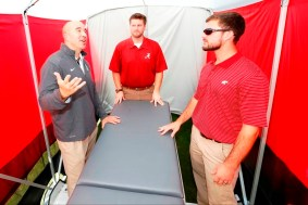 Co-inventors Jeff Allen, Jared Cassity and Patrick Powell stand inside the SidelinER. (University of Alabama)