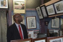 Tim Lewis looks at the civil rights memorabilia in Linton's Barber Shop, a landmark in Tuscaloosa's civil rights history that Lewis hopes will become part of a Tuscaloosa Civil Rights Trail. (Karim Shamsi-Basha/Alabama NewsCenter)