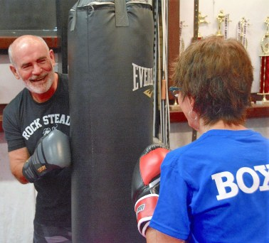 Gary Ellis helps another boxer practice. (Karim Shamsi-Basha / Alabama NewsCenter)