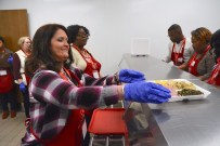 Wendy Malone picks up a meal she will serve to a member of a hungry crowd at The Salvation Army Thanksgiving lunch. (Karim Shamsi-Basha / Alabama NewsCenter)