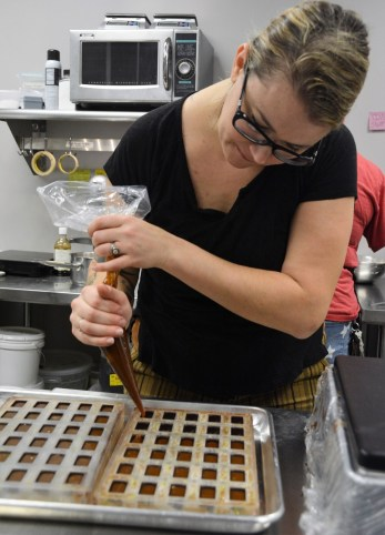 Michelle Novosel works in the kitchen of Pizzelle's Confections. (Karim Shamsi-Basha / Alabama NewsCenter)