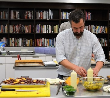 Chef Mauricio Papapietro composes brisket on a buttermilk cheddar biscuit with homemade pickles and whole grain white barbecue sauce. (Michael Tomberlin / Alabama NewsCenter)