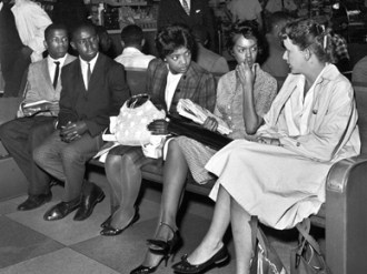 "Freedom Riders, from left, John Lewis, Charles Butler, Catherine Burks Brooks, Lucretia Collins and Salynn McCollum sit on a bench in the Birmingham Greyhound station on May 17, 1961. Soon after the photo was taken, the group was arrested and later released in a rural all-white area on the orders of Birmingham's commissioner of public safety, Eugene ""Bull"" Connor. (From Encyclopedia of Alabama, courtesy of The Birmingham News)"