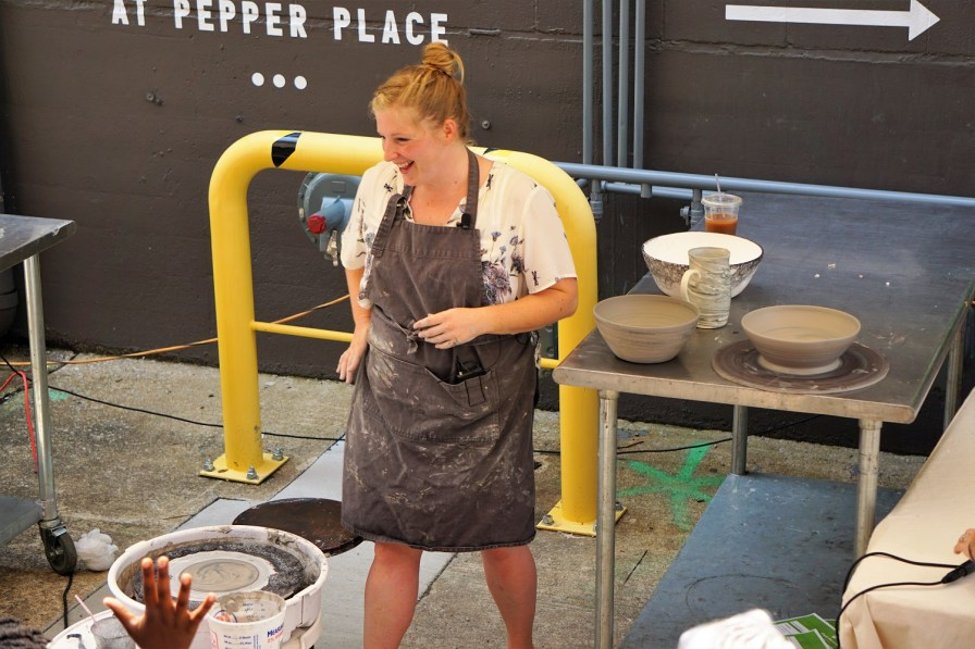 Lana Hobbs holds a pottery demonstration at Pepper Place on market day. (Erin Harney/Alabama NewsCenter)