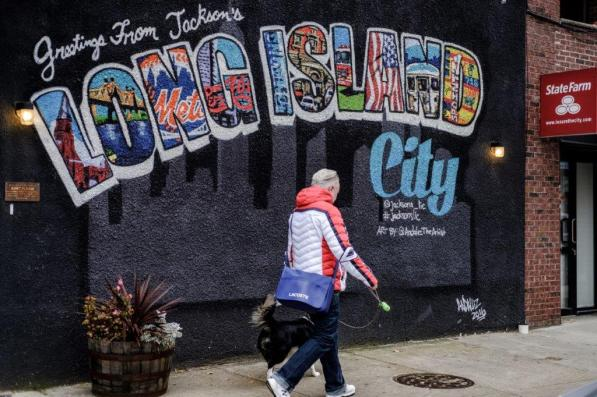 A pedestrian walks past a mural in the Long Island City neighborhood in the Queens borough of New York, one of two cities chosen for a split Amazon.com second headquarters. (Christopher Lee/Bloomberg)