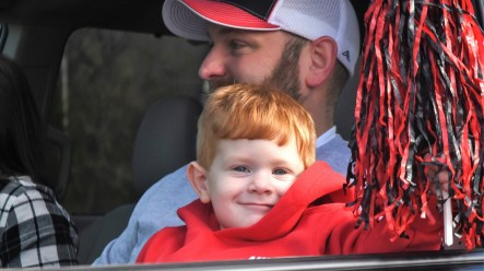 Ryan Johnson, 2, and his father, Matt, wait for the buses carrying the Thompson football team to pass. (Solomon Crenshaw Jr./Alabama NewsCenter)