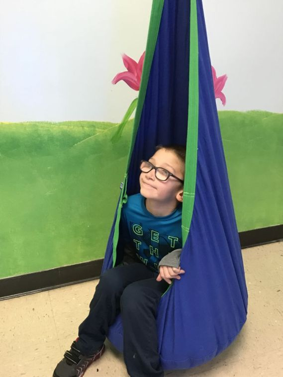 Jaycen tries out a hanging chair. (Donna Cope/Alabama NewsCenter)