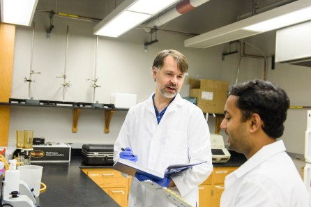 Dr. Mark Elliott, left, talks with Parnab Das as he works with water samples in the lab. (University of Alabama)