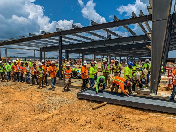Crew members sign the last beam to be installed on the Open Air Club before it is lifted into place at Talladega Superspeedway. (Dennis Washington / Alabama NewsCenter)