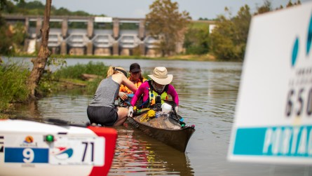 A team of racers prepares to get back in the water at the first portage. (Dennis Washington / Alabama NewsCenter)