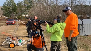 Drake Arden learns how to shoot a shotgun with the help of volunteers. (Dennis Washington / Alabama NewsCenter)