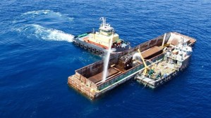 Water is sprayed into a barge containing an old Alabama Power boiler to submerge it into the Gulf waters in 2016. The artificial reef is now teeming with life. (file)