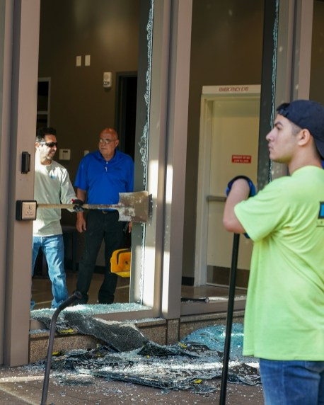 Workers clean up glass around the Harbert Center today after a protest Sunday evening. (Marvin Gentry/The Birmingham Times)
