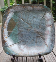 """Laura Jordan of McCalla-based Wheel Turned Pottery presses a collard green leaf into each """"Only In the South"""" piece before the clay is fired. (contributed)"""