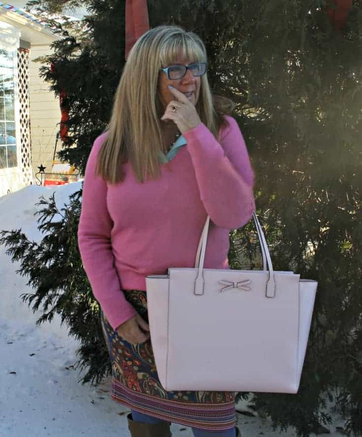 a pink cashmere sweater and kate spade bag
