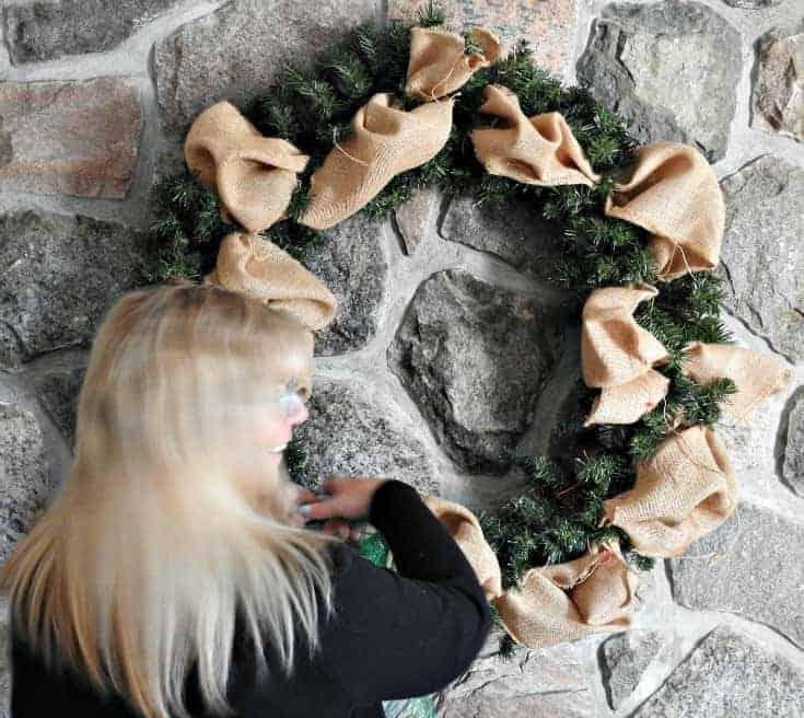 adding green decomesh ribbon to a wreath