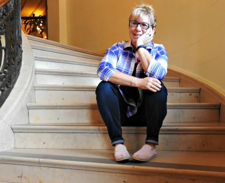 sitting in Old Navy Plaid and Haggar Dream Jeans with a Flaunt it 7 Charming Sisters necklace at the Chateau Laurier