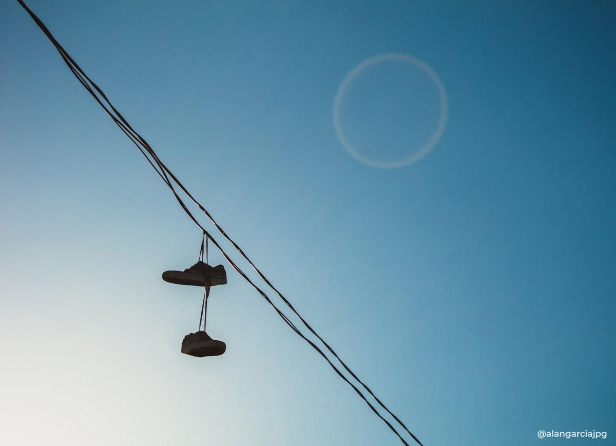 Par de tenis colgados en un cable de luz eléctrica.