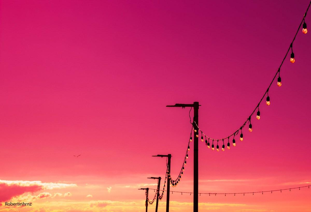 Contraluz de postes con cielo rojizo.
