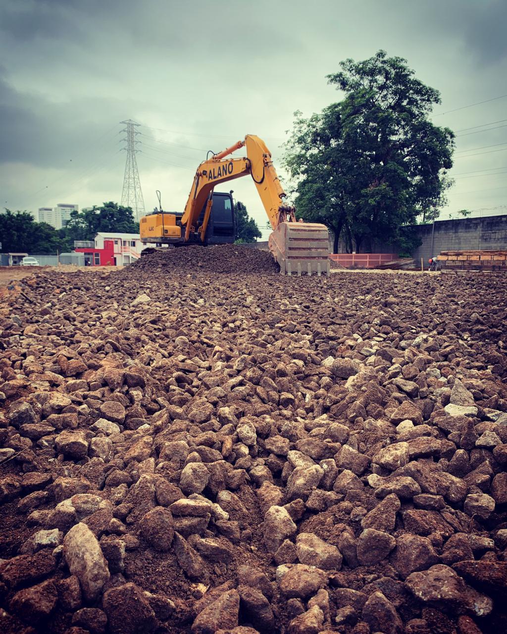 Escavadeira efetuando serviço em obra.