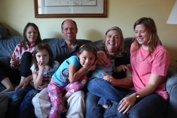 The Lohrey family. From left to right: Elena, Kylie, John, Kristyanna, Diane (holding a foster child) and Emilyanne. Elena, Kylie and Kristyanna have all been diagnosed with FASD. (Photo by Lisa Phu/KTOO)