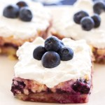These easy Lemon Blueberry Cheesecake Bars are made with fresh blueberries and a lemon shortbread crust! This homemade cheesecake recipe is topped with homemade whipped cream and blueberries! This is the perfect spring and summer dessert!