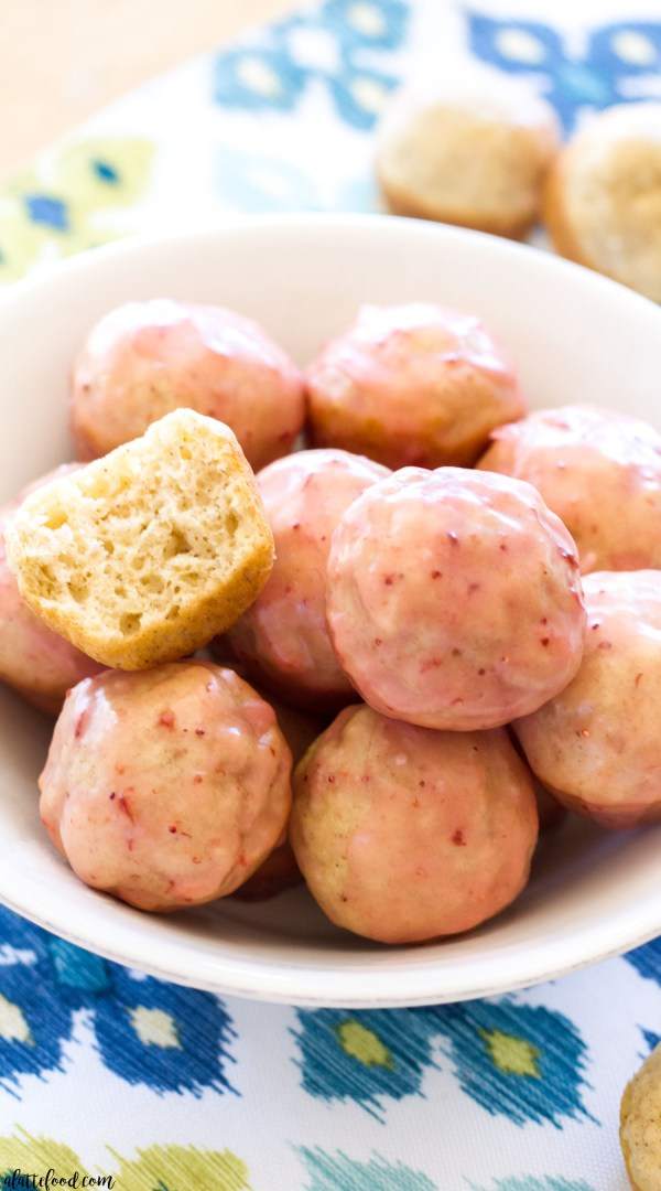 These easy homemade donut holes are baked not fried! They are dunked in a homemade strawberry glaze, making this donut hole recipe the perfect spring dessert or brunch!