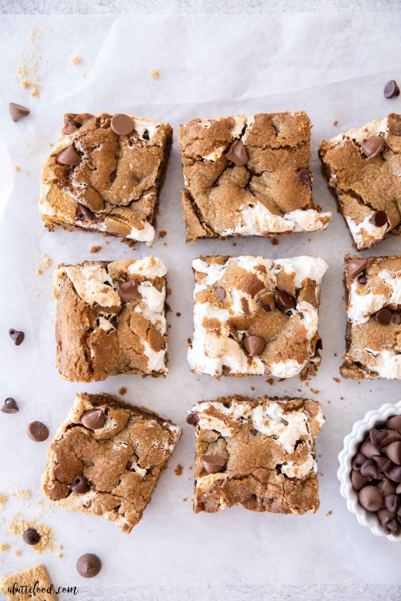 s'more chocolate chip cookie bars cut into squares on parchment paper