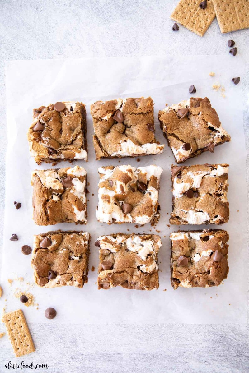 chocolate chip s'more cookie bars cut into squares on a gray marble board