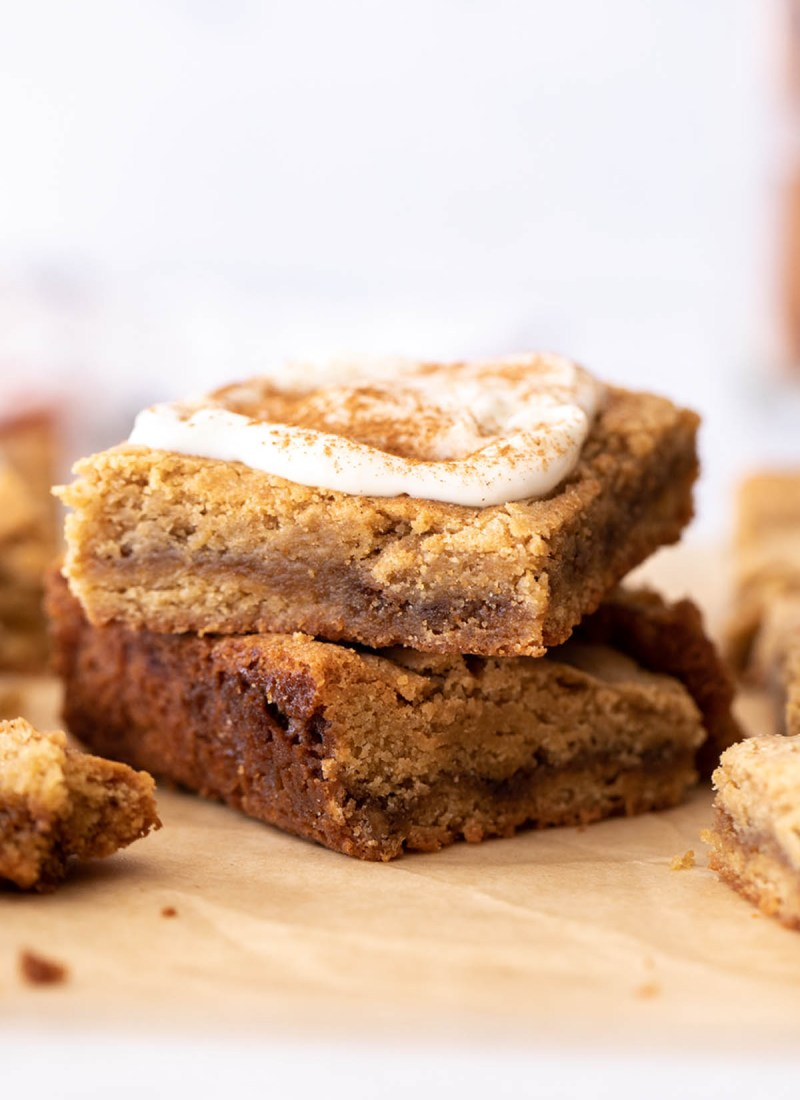 two cinnamon roll blondies with cream cheese frosting stacked on brown parchment paper