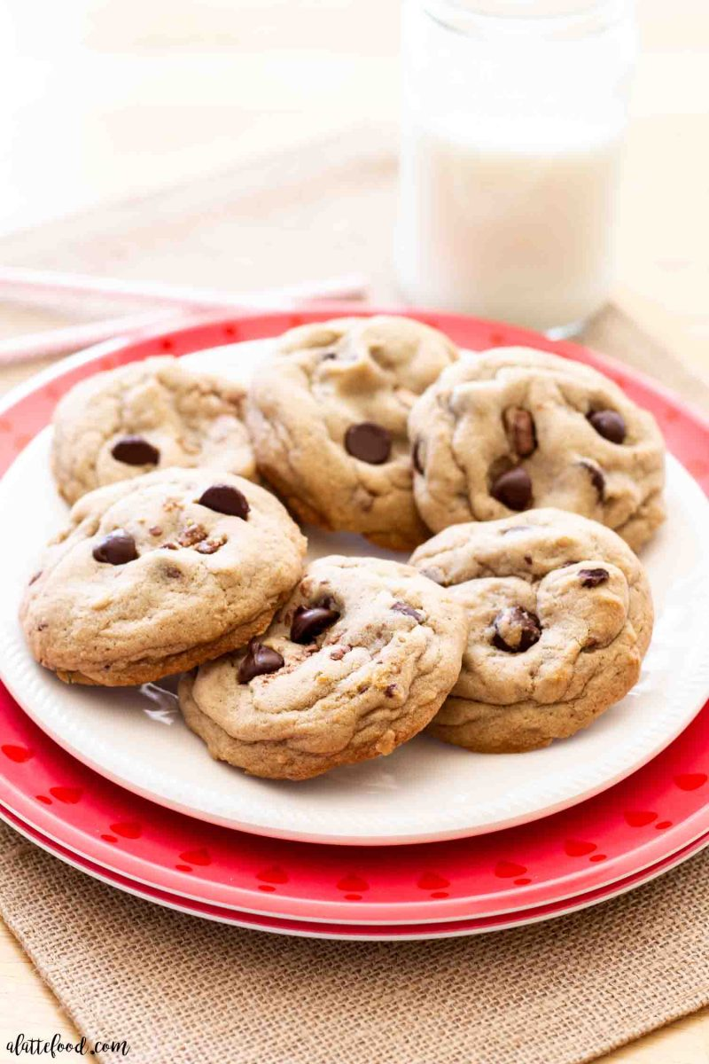 six chocolate chip toffee cookies on a white plate with a glass of milk