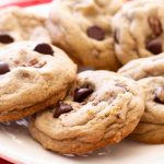 baked dark chocolate chip cookies with toffee bits on a red plate