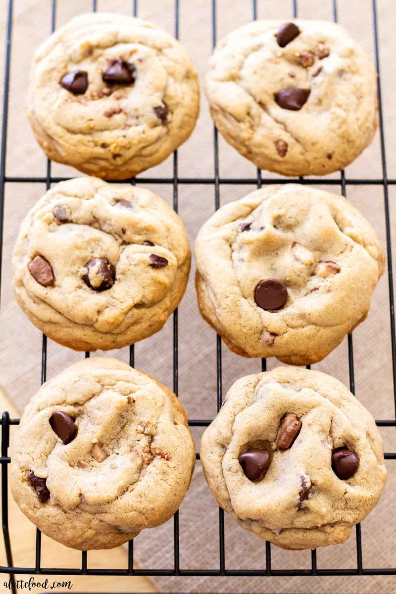 dark chocolate chip cookies with toffee bits on a wire cooling wrack