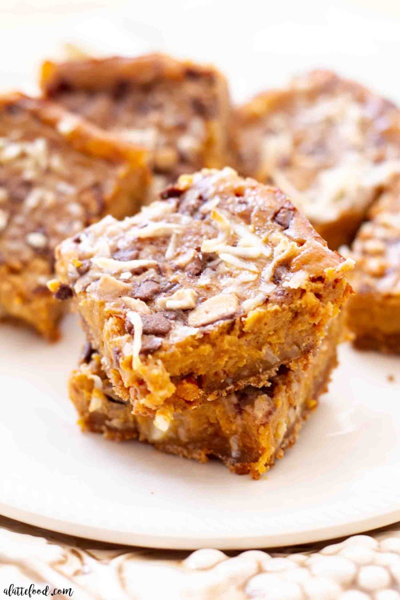 pumpkin pie dream bars baked and stacked on white dish