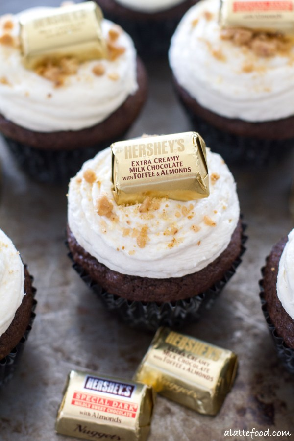 These rich chocolate cupcakes are topped with creamy vanilla buttercream, and are decorated with chocolates, toffee, and crushed graham crackers to look like hidden treasure! Perfect for a pirate themed party. | www.alattefood.com