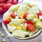 This summer salad is full of English cucumbers, tomatoes, roasted corn, Feta cheese, and avocado! | www.alattefood.com