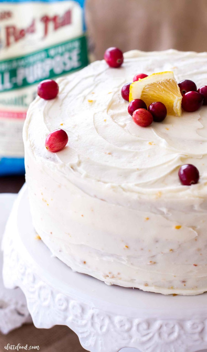 cranberry orange cake on white cake stand