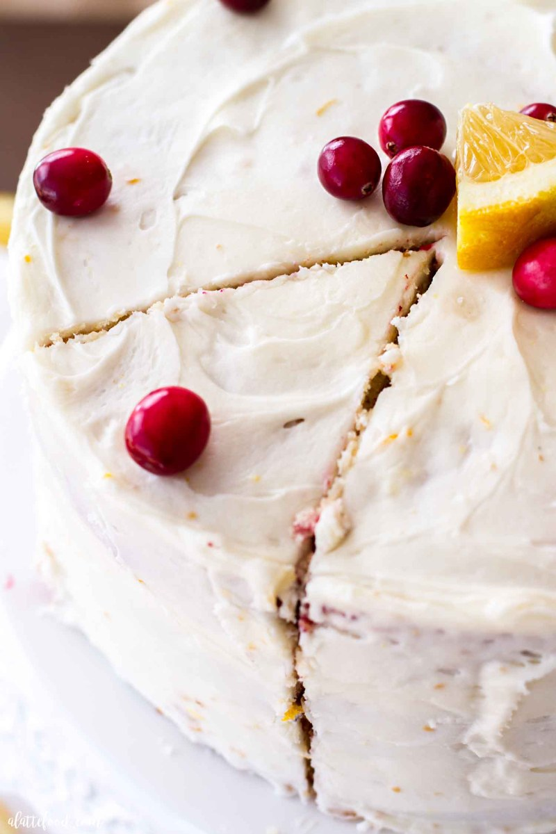cut slice of cranberry orange cake on white cake platter