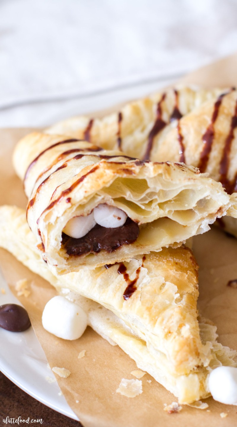 This easy s'mores turnover recipe is made with only 3-ingredients! Warm chocolate and gooey marshmallows stuffed inside flaky pastry dough? Homemade s'mores turnovers are always a crowd favorite! turnovers, chocolate, s'mores