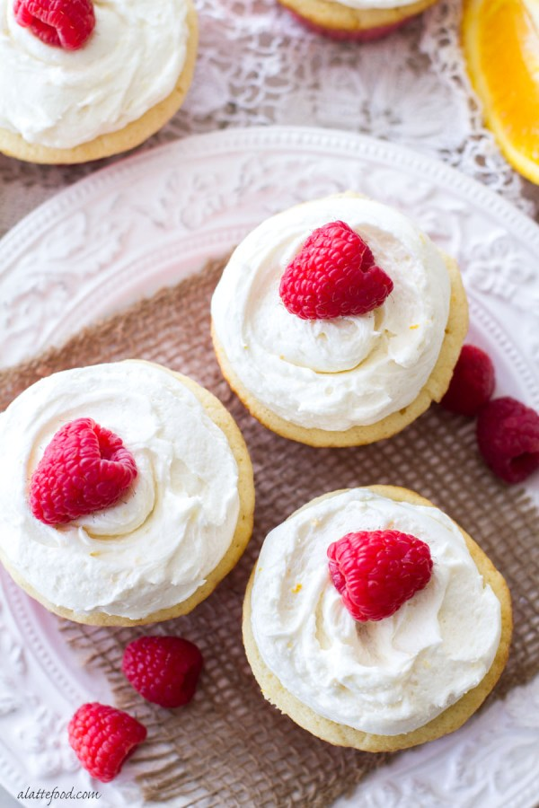 These sweet orange cupcakes are filled with a homemade raspberry cream and topped with an orange buttercream frosting! The flavors of spring in one simple homemade raspberry orange cupcake recipe.   www.alattefood.com