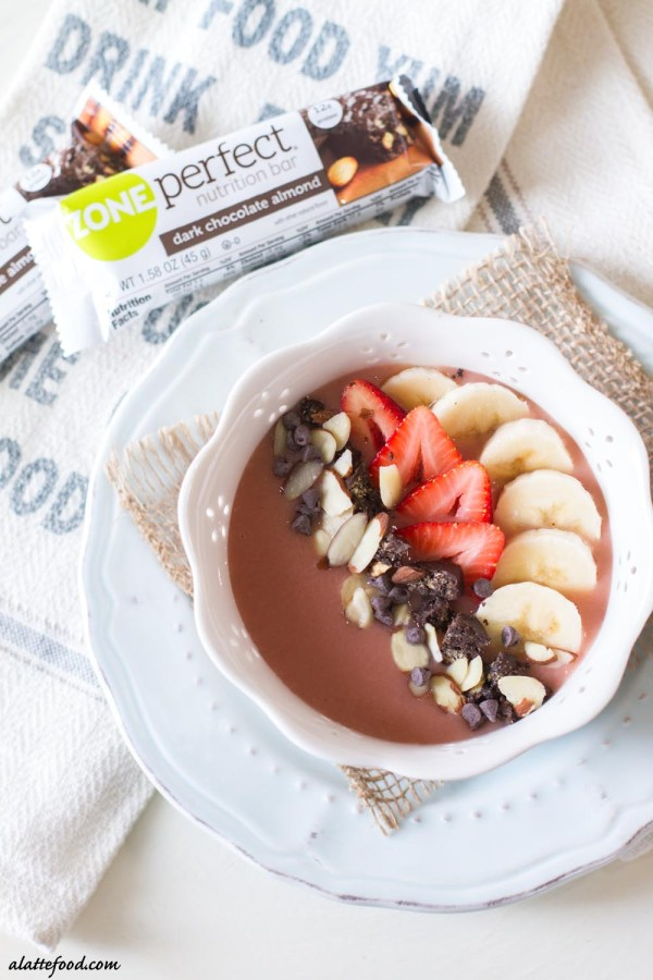 This pretty in pink chocolate strawberry banana smoothie bowl is made with fresh ingredients and topped with fresh fruit, sliced almonds, and dark chocolate chips!